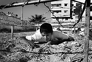 A Palestinian boy crawls under a barb wire platform during HAMAS sponsored summer camp August 04, 2007 in Gaza City, Gaza. Kids from age 7 to 16 are given military style training 6 days a week at HAMAS camps like this across Gaza for 3 hours per day.