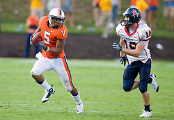 Virginia running back Mikell Simpson (5) rushes past Richmond defensive back Michael Ireland (18).  The Virginia Cavaliers defeated the #3 ranked (NCAA Division 1 Football Championship Subdivision) Richmond Spiders 16-0 in a NCAA football game held at Scott Stadium on the Grounds of the University of Virginia in Charlottesville, VA on September 6, 2008.