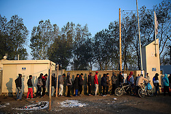 © Licensed to London News Pictures. 25/10/2016. Calais, France.  Migrants queue to use the showers at sunrise at the migrant and refugee camp in Calais, known as the 'Jungle'. French authorities have moved thousands of refugees and migrants living at the makeshift living area on the French coast, with some still refusing to leave. . Photo credit: Ben Cawthra/LNP