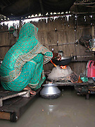 Jahura Khatun cooks lunch on her bed/platform as floodwaters inundate her house at Sialmari, about 329 kilometers southwest of Gauhati, the capital city of Northeastern Indian state, Assam, Monday, June 28, 2004. ..Floodwaters of the Asia'a one of the largest river, Brahmaputra and its 35 tributaries have affected more than one million in all of Indian subcontinent and disrupted communication in many parts of the India and Bangladesh, sources said.  (AP Photo/ Shib Shankar Chatterjee).