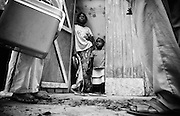 A woman and her child stand in the doorway of their home during the visit of a polio vaccination team in Djambala, Republic of Congo on Wednesday December 8, 2010.