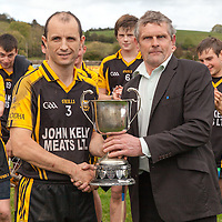 Ballyea's Captain Frankie Griffin accepts the Junior B Hurling Cup from Cllr. Joe Cooney