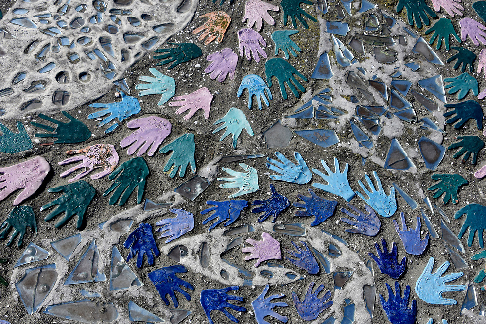 Hand prints in various shades of blue as tiles on an outside path, near the sea