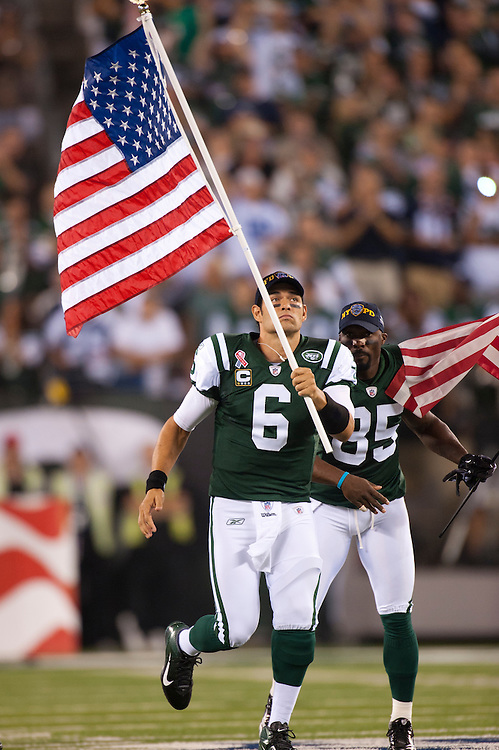 EAST RUTHERFORD, NJ - SEPTEMBER 11: Mark Sanchez #6 of the New York Jets runs onto the field carrying an American Flag honoring the tenth anniversary of 9/11 before the game against the Dallas Cowboys at MetLife Stadium on September 11, 2011 in East Rutherford, New Jersey. The Jets defeated the Cowboys 27 to 24. (Photo by Rob Tringali) *** Local Caption *** Mark Sanchez