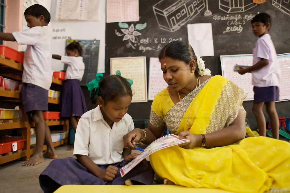 At Periyakuppam village primary school, in tsunami-affected Cuddalore district, all 1-4 Grade students (87 pupils) are completing the ABL curriculum. Almost all of these students are  tsunami-affected and from poor fishing families. With the assistance of Unicef and the Tamil Nadu Government, the school has been pursuing ABL since 2005 and is one of the model schools for the government's wider implementation of the program. Unicef has supplied the school teaching advice, tables, and learning equipment including the activity cards that are the basis of ABL learning. ..ABL (Activivity Based Learning) was first implemented in Chennai City government schools. Such was the success of the program that Unicef developed the model and worked with the Tamil Nadu government to introduce it to all 330 schools in the three tsunami affected districts of Cuddalore, Nagappatinam and Kanyakumari. On the basis of the tsunami-schools' experience, the Government of Tamil Nadu has now applied the scheme for all 1-5 Grade students in all government schools in the state. ABL encourages children to learn at their own pace, individually or in small groups. It dispenses with the idea of the class teacher standing at the blackboard with all pupils looking forward. Children are inspired to consider learning a creative and enjoyable experience. Using a series of task-cards, students are taught to take responsibility for their own achievements and to pursue their studies at a steady pace. The class teacher is on hand for any assistance required by pupils. Unicef has provided learning materials, tables and advice to the Tamil Nadu government. Other Indian state education administrations are now looking to Tamil Nadu with the idea that they might themselves implement ABL...Cuddalore, Tamil Nadu, India.December 8th 2008..THIS PHOTOGRAPH IS THE COPYRIGHT OF TOM PIETRASIK. THE PHOTOGRAPH MAY NOT BE REPRODUCED IN ANY FORM OTHER THAN THAT FOR WHICH PERMISSION WAS GRANTED. THE PHOTOGRAPH MAY NOT BE MANI