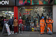 Construction workers and shop mannequins stand outside a budget store in Oxford Street, on 12th December 2017, in London England.