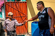 "A man pays 20 pesos ($1 US) to the water delivery crew as a ""tip"", though according to government policy, the water should be free."
