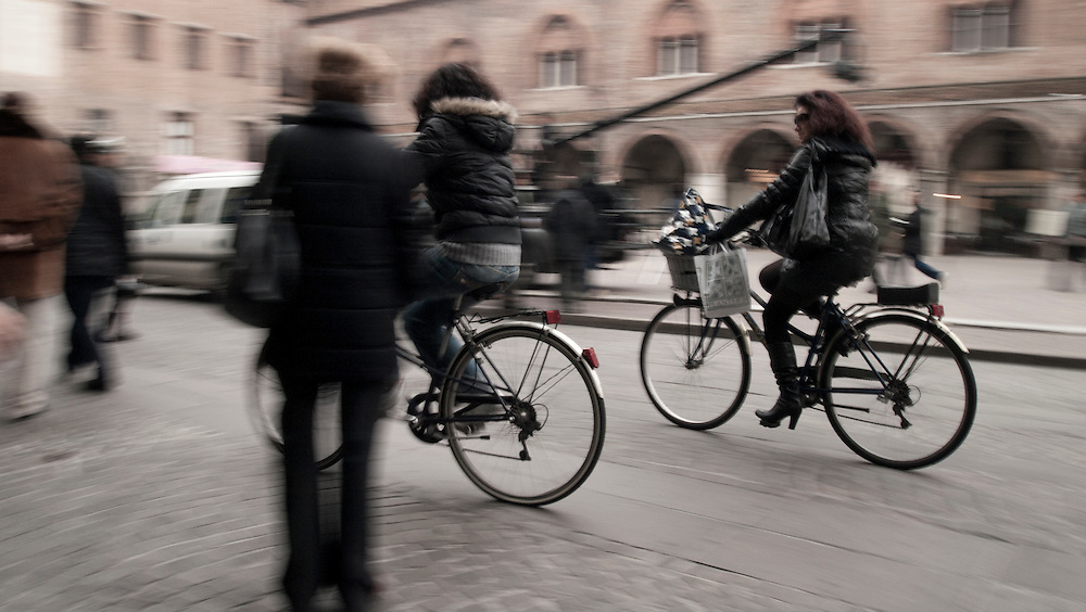 Cyclists on the Piazza delle Erbe Montova. A series of captures from a personal trip to the cities of Milan and Mantua, featuring explorations of Renaissance architecture and the vibrant life of Italian streets.