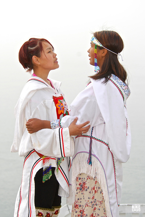 Model released inuit teens throat singing, wearing their traditional clothing. (MR). Pond Inlet, Baffin Island. High Arctic. Canada<br /> ( isolated, remote, tourist, hike, hiking, foggy, weather, rock, rockly. tongue, indigenous, local, folklore, dress, boots,.