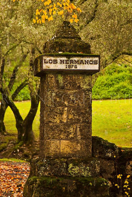 Los Hermanos 1876 pillar in front of Beringer Vineyards along the historic tunnel of Elms in Saint Helena, California. Napa Valley.