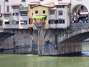 The Ponte Vecchio medieval stone closed-spandrel segmental arch bridge over the Arno River, in Florence, Italy, noted for still having shops built along it, as was once common. It was rebuilt in 1345