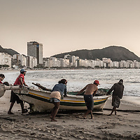 Brazilian fishermen launch a brightly painted fishing boat on a tranquil morning on Copacabana Beach.