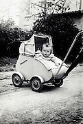 vintage photo of a toddler outside in a stroller