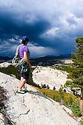 Climber on Marmot Dome watching storm over Tuolumne Meadows, Yosemite National Park, California USA