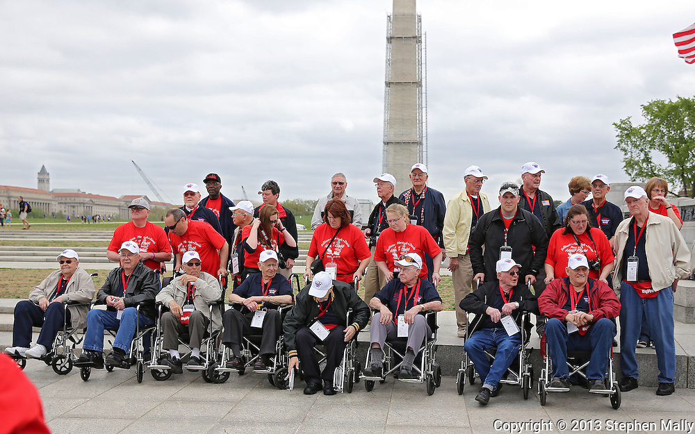 The first of the three busloads of Veterans and guardians pose for a picture during the Sullivan-Hartogh-Davis Post 730 Honor Flight at the National World War II Memorial in Washington, DC on Tuesday, April 16, 2013. About 90 veterans were on the trip. After their visit to the National World War II Memorial they would take a bus tour of Washington, DC followed by a visit to the Korean War Veterans Memorial.