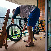 Andrew Whiteford works on his bike in the early morning hours at the Marisa Boutique Resort in the jungle near Chiang Dao, Thailand.