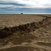 Two distant figures sitting on sandy beach