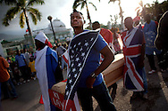 "Men wearing flags representing the UN and countries with past and present interests in Haiti, carry a coffin draped in a Haitian flag with a placard reading ""what life"" march past the earthquake-destroyed Haitian national palace on the first day of the Port-au-Prince carnival celebration, March 6, 2011 in Port-au-Prince, Haiti-- over a year after the earthquake.  Last year's celebration was cancelled."