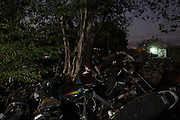 Motorbikes piled up rot away in Bangkok's 'car cemetery'. <br /> <br /> According to a 2014 study by the University of Michigan&rsquo;s Transportation Research Institute Thailand ranks number 2 in the world for road fatalities, narrowly second only to Namibia. The report found a frightening 44 road deaths were recorded per 10,000 population. The high accident rate is often attributed to reckless driving, including driving while intoxicated, and lack of safety precautions such as wearing a helmet on motorbikes. A WHO report indicated that 26 percent of road deaths in Thailand involve alcohol.<br /> <br /> The sheer number of crashed vehicles is so high that police now hold auctions to sell off the vehicles, either not wanted by their owner or beyond repair, and it has become a good business. But the auctions are a relatively new phenomenon where previously cars would be kept at police stations until the legal case is complete and then deposited at a collection site.<br /> <br /> On the outskirts of Bangkok in a scruffy suburb is one such depository. Dubbed &lsquo;the car cemetery&rsquo; by locals it was where many of Bangkok&rsquo;s damaged wrecks would end up if no-one else wanted to them. But the site has also taken on another reputation; that of being one of the most haunted places in the city, third to be precise according to a local TV station. Thai&rsquo;s are very superstitious people and most believe in ghosts or spirits. Here it was believed that the spirits of those killed in the crashes remained with the vehicles they died in. Many a passerby or taxi driver have stories of people in and around the compound who then simply vanishing. Locals became so frightened of the place that a group of Thai Buddhist monks from a nearby temple were invited in to perform a ritual exorcism to release the spirits.<br /> <br /> With most crashed cars now being bought at the auctions the car cemetery doesn&rsquo;t receive new vehicles anymore but many of the old ones remain surrounded by weeds and covered in rust. Grotesque relics and unwanted wr