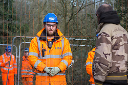 Harefield, UK. 7 February, 2020. An activist observes HS2 engineers in the process of erecting Heras fencing to surround three environmental activists from Extinction Rebellion who have climbed a veteran oak tree close to the Harvil Road wildlife protection camp in order to try to protect it from felling. HS2 are expected to try to fell large numbers of mature trees in the immediate vicinity over the weekend even though the high-speed rail link is still awaiting Boris Johnson's approval.