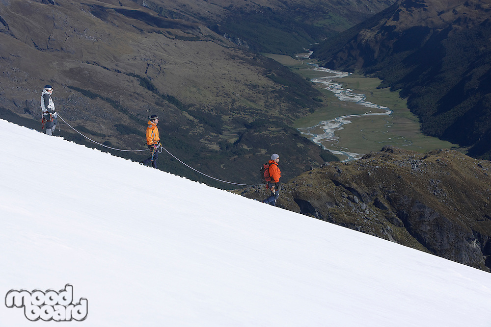 Mountain climbers descending snowy slope