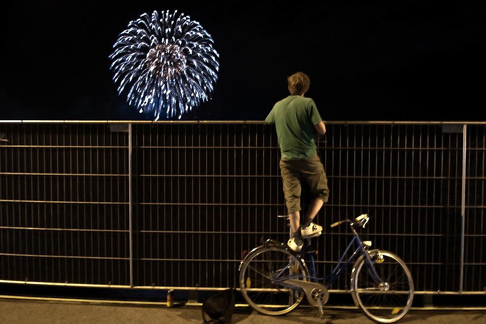 A young man standing on a bike at the Zoobrücke, a bridge  is watching the Kölner Lichter / Cologne lights a firework over the river Rhein / Rhine. Ein junger Mann steht auf einem Fahhrad um über den Sichtschutz eines Zaunes auf der Zoobrücke zu schauen, danmit er das Feuerwerk der Kölner besser Lichter beobchten kann.
