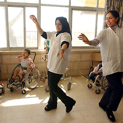 AZZARIYA, WEST BANK, MARCH 5: Nurses sing and dance to mentally disabled, autistic and physically handicapped Palestinians and others who have no family or have been abandoned March 5, 2003 in Arba'at Batei Hahemla (Four Houses of Mercy) in Azzariya, West Bank. It was founded in 1940 by the late Palestinian philanthropist Catherine Siksek and is one place in the occupied territories where dozens of Palestinians and some of society's weakest members find protection and care. Outside their is war, destruction, poverty and humiliation but inside it is a place of joy where none of the devastaton has been allowed to penetrate.  The doctors and nurses work grueling days for little pay and often spend 4 hours a day just to travel a few miles to get through Israeli checkpoints but it never deters them.  (Ami Vitale/Getty Images)