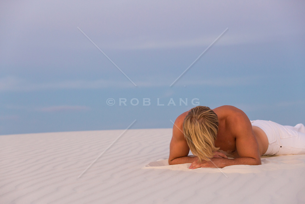 blond shirtless man with his head down in a sand dune