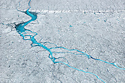Meltwater flows thru a low area of the Greenland ice sheet that had previously been deposited dark with cryoconite, 70km southeast of Ilulissat, August, 2014. The presence of cryoconite, or ash and soot deposited on top of the ice sheet, triples the melt rate atop the ice sheet.