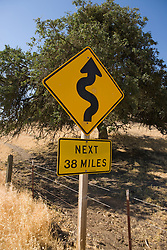 A yellow highway sign indicating that the next 38 miles will be winding turns, California, USA.