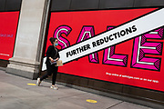 On the day that covid pandemic guidelines for shoppers in England mean that the wearing of face coverings in shops is mandatory, shoppers walk past Sales windows of Seflridges on Oxford Street in the capital's West End, on 24th July 2020, in London, England.