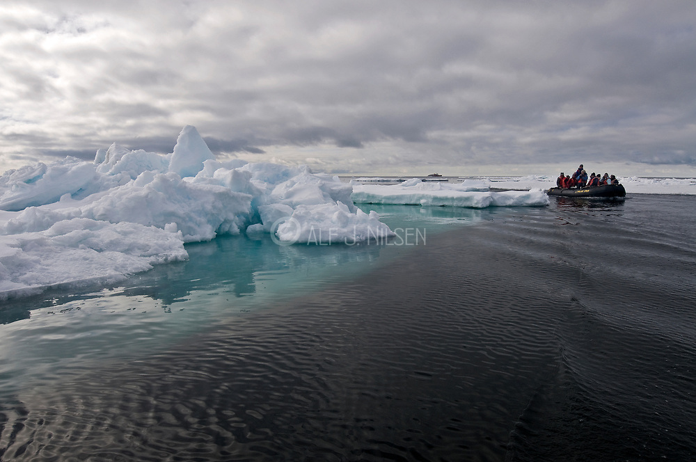 Eco-tourists approaching a huge ice berg at about 80-degrees north at Spitsbergen in June 2008.