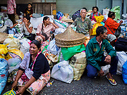 18 SEPTEMBER 2017 - BANGKOK, THAILAND: People sit among the food they received during a food giveaway at Poh Teck Tung in Bangkok. The Ghost Festival, also known as the Hungry Ghost Festival, Zhongyuan Festival or Yulan Festival is a traditional Buddhist and Taoist festival held in Asian countries. According to the Chinese calendar (a lunisolar calendar), the Ghost Festival is on the 15th night of the seventh month. In Chinese culture, the fifteenth day of the seventh month in the lunar calendar is called Ghost Day and the seventh month in general is regarded as the Ghost Month, in which ghosts and spirits, including those of the deceased ancestors, come out from the lower realm. Distinct from both the Qingming Festival (in spring) and Double Ninth Festival (in autumn) in which living descendants pay homage to their deceased ancestors, during Ghost Festival, the deceased are believed to visit the living.     PHOTO BY JACK KURTZ