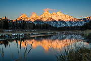 Sunrise spotlights the Tetons which reflect beautifully in the Snake River at Schwabacher Landing (16 miles north of Jackson Hole on US26/89/191). Grand Teton National Park, Wyoming, USA.