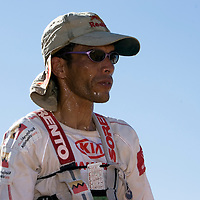 28 March 2007: Nine times winner of the men race Lahcen Ahansal of Morocco rests a few seconds at check point 4 during fourth and longest stage of the 22nd Marathon des Sables between jebel Zireg and west of Kfiroun (43.8 miles). The Marathon des Sables is a 6 days and 151 miles endurance race with food self sufficiency across the Sahara Desert in Morocco. Each participant must carry his, or her, own backpack containing food, sleeping gear and other material.