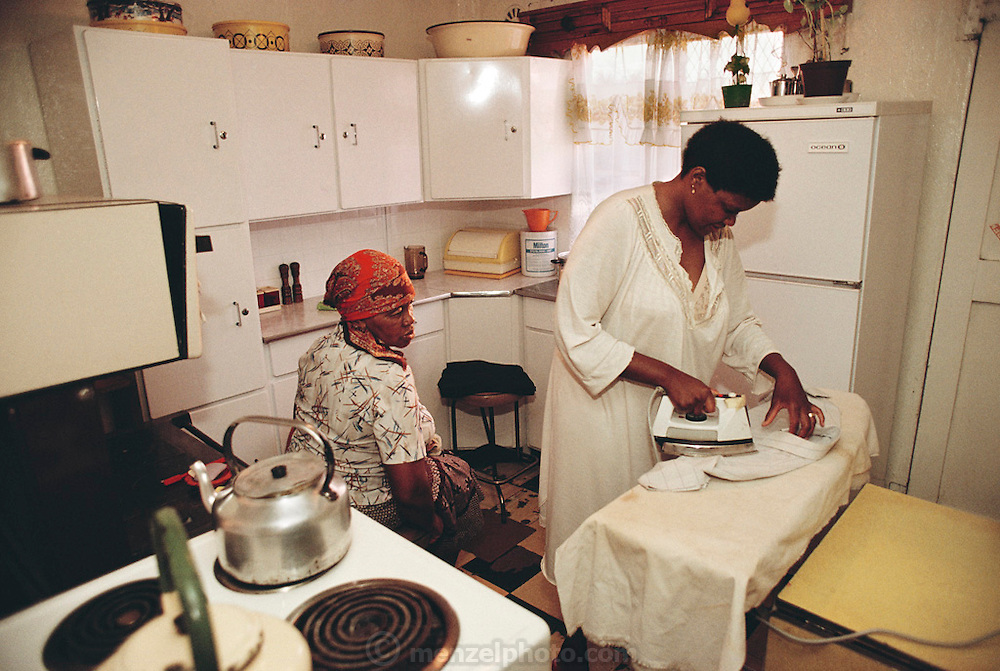 Poppy Qampie irons Simon's shirt in the kitchen of their Soweto home before she leaves for work as her mother, Leah, looks on. The Qampie family lives in a 400 square foot concrete block duplex house in the sprawling area of Southwest Township (called Soweto), outside Johannesburg (Joberg), South Africa. Material World Project.