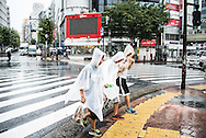 Kids walking under the rain. Typhoon number 10 called Lionrock hit japan early on morning, in Tokyo. 30/08/2016-Tokyo, JAPAN