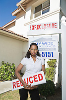 Woman holing sign outside house