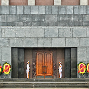 Two soldiers in ceremonial uniforms stand guard in front of the Ho Chi Minh Mausoleum, dwarfed by the granite blocks of the building. A large memorial in downtown Hanoi surrounded by Ba Dinh Square, the Ho Chi Minh Mausoleum houses the embalmed body of former Vietnamese leader and founding president Ho Chi Minh.