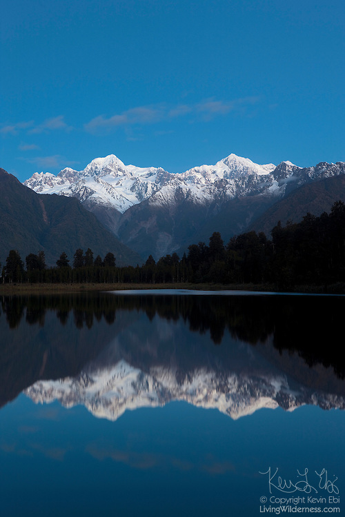 Mounts Tasman and Cook, New Zealand's two tallest mountains, are reflected in the still waters of Matheson Lake just after sunset. Tasman, at left, is 3497 metres (11,473 feet); Cook is 3754 metres (12,316 feet.) Both mountains are part of New Zealand's Southern Alps and are located in Westland National Park. Mount Cook is also known as Aoraki, the name it was given by New Zealand's first settlers.