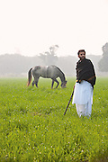 Ali Mohammad Khan stands in a field near the Mehmudabad Qila.