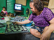"28 OCTOBER 2014 - BANGKOK, THAILAND: A worker drops batter into cake cups at the Pajonglak Maneeprasit Bakery in Bangkok. The cakes are called ""Kanom Farang Kudeejeen"" or ""Chinese Monk Candy."" The tradition of baking the cakes, about the size of a cupcake or muffin, started in Siam (now Thailand) in the 17th century AD when Portuguese Catholic priests accompanied Portuguese soldiers who assisted the Siamese in their wars with Burma. Several hundred Siamese (Thai) Buddhists converted to Catholicism and started baking the cakes. When the Siamese Empire in Ayutthaya was sacked by the Burmese the Portuguese and Thai Catholics fled to Thonburi, in what is now Bangkok. The Portuguese established a Catholic church near the new Siamese capital. Now just three families bake the cakes, using a recipe that is 400 years old and contains eggs, wheat flour, sugar, water and raisins. The same family has been baking the cakes at the Pajonglak Maneeprasit Bakery, near Santa Cruz Church, for more than 245 years. There are still a large number of Thai Catholics living in the neighborhood around the church.   PHOTO BY JACK KURTZ"