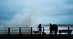 © Licensed to London News Pictures. <br /> 21/03/2015. <br /> <br /> Sandsend, North Yorkshire.<br /> <br /> Huge waves crash against the sea wall at Sandsend in North Yorkshire as a group of friends walk past. The exceptionally high Spring tides were created by the moon's 18-year cycle.<br /> <br /> Photo credit : Ian Forsyth/LNP