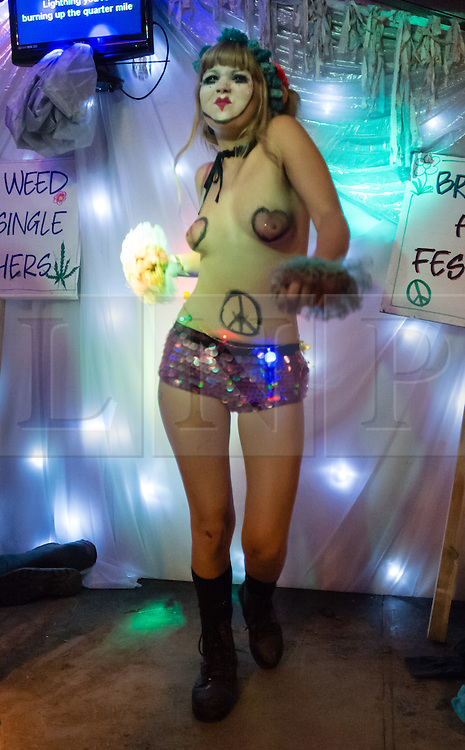 © Licensed to London News Pictures. 27/06/2015. Pilton, UK.  Night-time festival atmosphere at Glastonbury Festival 2015 in the Shangri-La area of the festival - a topless female performer.  On Saturday Day 4 of the festival.  Shangri-La is a destroyed dystopian pleasure city.  This years headline acts include Kanye West, The Who and Florence and the Machine, the latter being upgraded in the bill to replace original headline act Foo Fighters. Photo credit: Richard Isaac/LNP