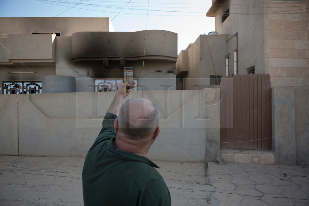 © Licensed to London News Pictures. 04/11/2016. Hamdaniyah, Iraq. A Christian resident of Hamdaniyah, Iraq, uses his mobile phone to take a picture to show damage to the house of a friend in the recently liberated town. The friend, like many residents, is afraid to return to the town due to its proximity to the nearby frontline and the numerous improvised explosive devices and pieces of unexploded ordnance that litter the settlement.<br /> <br /> Although located close to a front line, littered with improvised explosive devices and pieces of unexploded ordnance the Christian town of Hamdaniyah has only recently been cleared of ISIS extremists who stayed behind to fight. After the town's liberation as part of the Mosul Offensive residents and priests of the town are now free to take short trips to assess damage, salvage possessions and clear up the mess left by militants during their two year occupation.<br /> <br /> Hamdaniyah, and much of the Nineveh plains, were captured by the Islamic State during a large offensive on the 7th of August 2014 that saw the extremists advance to within 20km of the Iraqi Kurdish capital Erbil. Residents of the town, who included many Christian refugees who escaped there after the fall of Mosul, were then forced to seek sanctuary in the Kurdish areas. In the year and two months of the ISIS occupation churches were burnt, homes were put into use as militant accommodation and bomb factories and some buildings destroyed by coalition airstrikes. Photo credit: Matt Cetti-Roberts/LNP