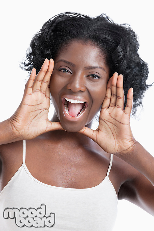Portrait of a playful young woman shouting over white background