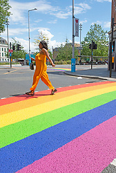 ©Licensed to London News Pictures 16/06/2020<br /> Woolwich, UK. A lady walking on a colourful crossing in Woolwich town centre, Woolwich. Rainbow pedestrian crossings return to Greenwich Borough to show support for Gay pride month. Crossings in Eltham,Greenwich, plumstead,Charlton and Woolwich have had a rainbow make over bringing some colour to the streets in South East London. Photo credit: Grant Falvey/LNP