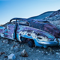 An antique car all shot up and rotting, located by an old mine site in Death Valley, California