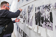 "Portland, Oregon, USA. 26 FEB, 2018. The photographer Robert Frank's work from his ground breaking book ""The Americans"" hangs  defaced as a gallery goer shreds it at Blue Sky Gallery in Portland, Oregon, USA. The work was destroyed in a ""Destruction Dance"" performance defacing the photographs with ink and mutilation with scissors, knives and even ice skates  at the end of it's run. The destruction was Frank's protest regarding today's greed in the global art market."