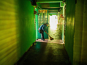 24 FEBRUARY 2015 - PHNOM PENH, CAMBODIA:  A woman sweeps the hallway in front of her apartment in the White Building. The White Building, the first modern apartment building in Phnom Penh, originally had 468 apartments, and was opened the early 1960s. The project was overseen by Vann Molyvann, the first Cambodian architect educated in France. The building was abandoned during the Khmer Rouge occupation. After the Khmer Rouge were expelled from Phnom Penh in 1979, artists and dancers moved into the White Building. Now about 2,500 people, mostly urban and working poor, live in the building. Ownership of the building is in dispute. No single entity owns the building, some units are owned by their occupants, others units are owned by companies who lease out apartments. Many of the original apartments have been subdivided since the building opened and serve as homes to two or three families. The building has not been renovated since the early 1970s and is in disrepair. Phnom Penh officials have tried to evict the tenants and demolish the building but residents refuse to move out.  PHOTO BY JACK KURTZ